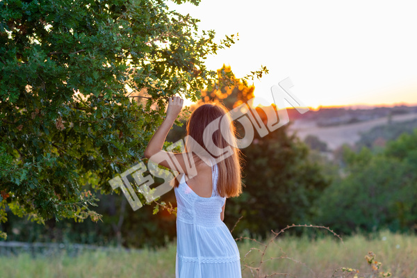 Profile of a young girl with long blond hair, dressed in white watching the setting sun while touching the magic tree in countryside