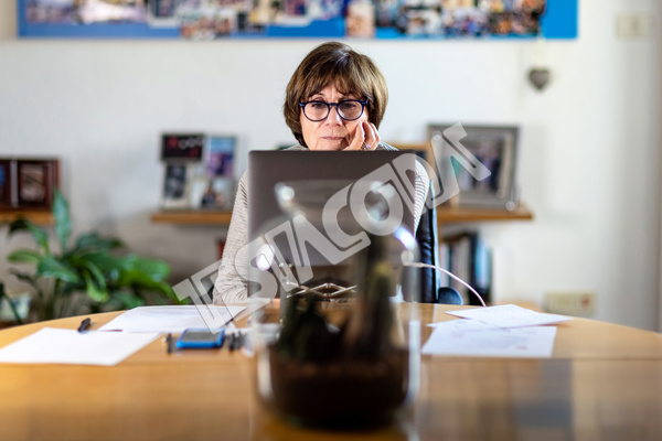 Aged lady Senior Consultant wearing glasses working remotely from home in a video meeting with her laptop on a wooden table with papers and pens