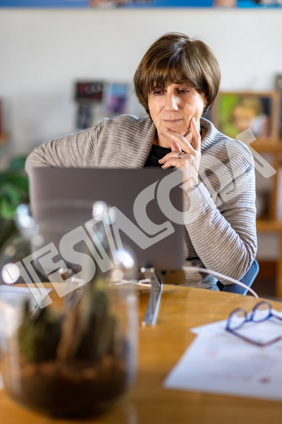Aged lady Senior Consultant with hand on cheek working remotely from home in a video meeting with her laptop on a wooden table with papers and glasses