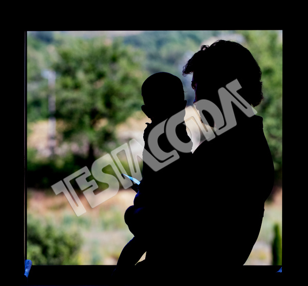 Backlight image of dad with his cute baby in his arms looking at smartphone at the window . In the blurred background green nature bushes and trees