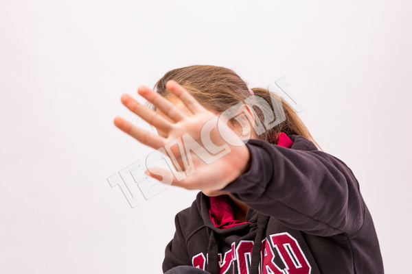 Young girl with sweatshirt hides her face and shields herself with her left hand blurred in the foreground not wanting to be photographed