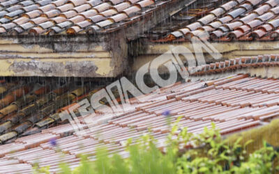 Pouring rain on tiles and gutters of a city roof (w/ sound)